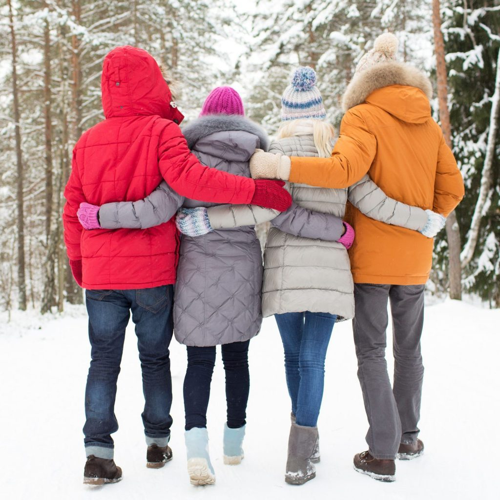 48379988 - love, relationship, season, friendship and people concept - group of happy men and women walking in winter forest